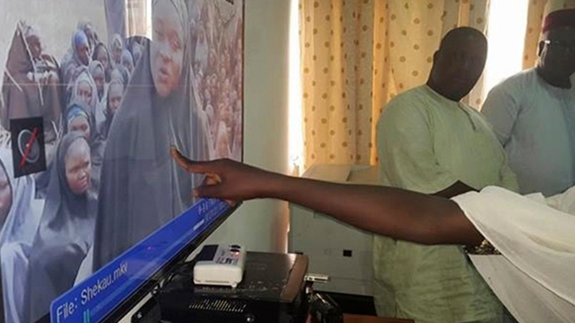 FILE 2014: A student who escaped when Boko Haram rebels stormed a school in May and abducted schoolgirls, identifies her schoolmates from a video released by the Islamist rebel group at the Government House in Maiduguri, Borno State.