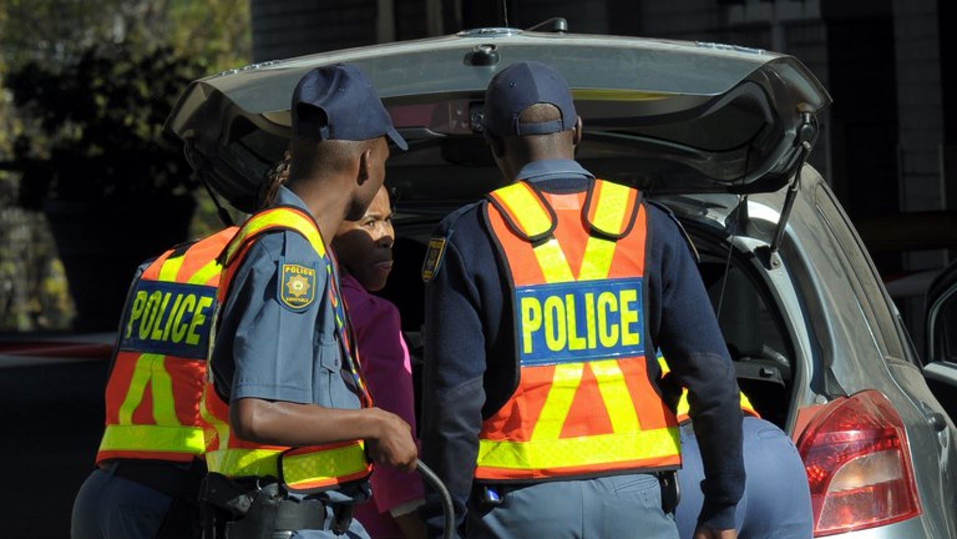 Police check people arriving at the Medi-Clinic Heart Hospital in Pretoria, last week. A South African police commander was found murdered in a field with his hands and feet bound in the early hours of Tuesday, a police commissioner said.