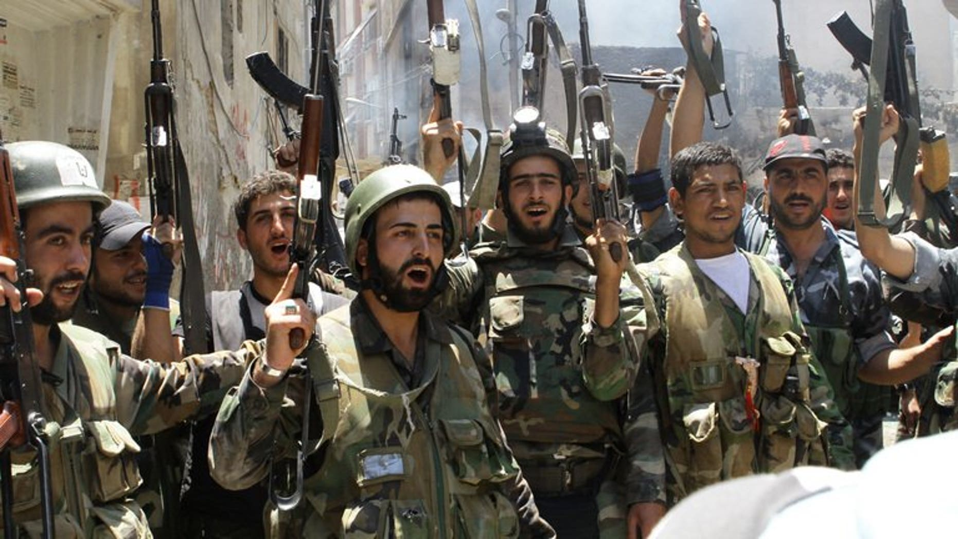 Syrian soldiers celebrate in the al-Midan area in Damascus on July 20, 2012. Troops loyal to Syrian President Bashar al-Assad pushed forward a bid to crush rebel bastions near the capital Damascus, a monitoring group and activists said.