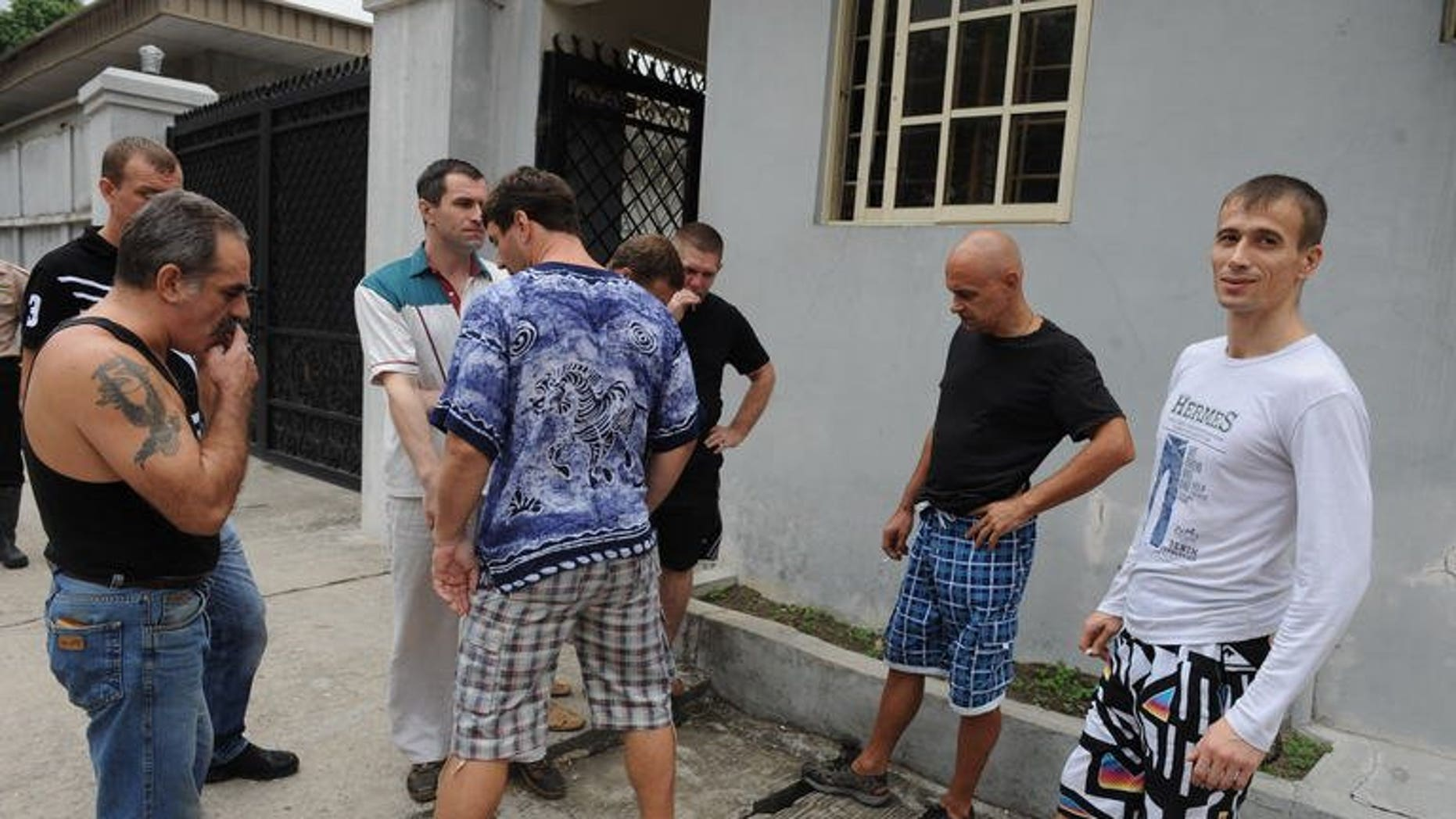 Russian sailors outside a Lagos courthouse on Tuesday during a hearing on claims of illegal possession of arms. The courtdismissed charges against eight of 15 Russian seamen arrested in October, but set a trial date for later this week for the others.