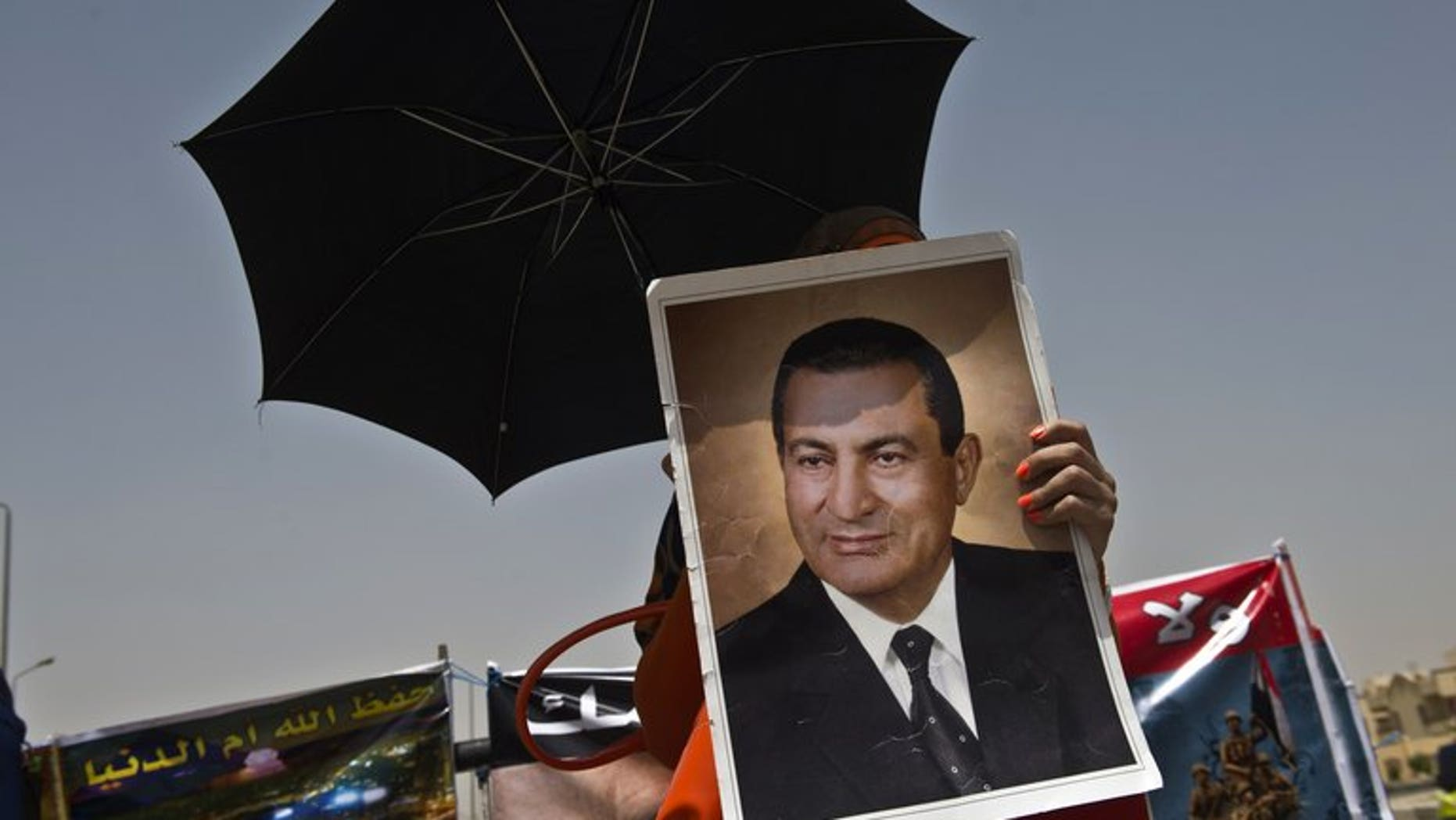 A supporter of Hosni Mubarak holds a portrait of him outside the court in Cairo last week during his retrial. An Egyptian court on Tuesday ended Mubarak's detention in one corruption case, judicial sources told AFP, but the ousted president will remain in custody on other charges.