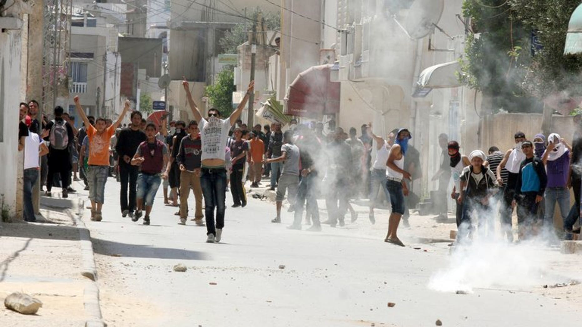 Tunisian police fire tear gas at radical Islamists in Ettadhamen, west of Tunis, in May. Six people belonging to Tunisia's hardline Salafist movement have each been handed five year jail sentences for torching an important Sufi shrine, the country's Sufi union said on Tuesday.
