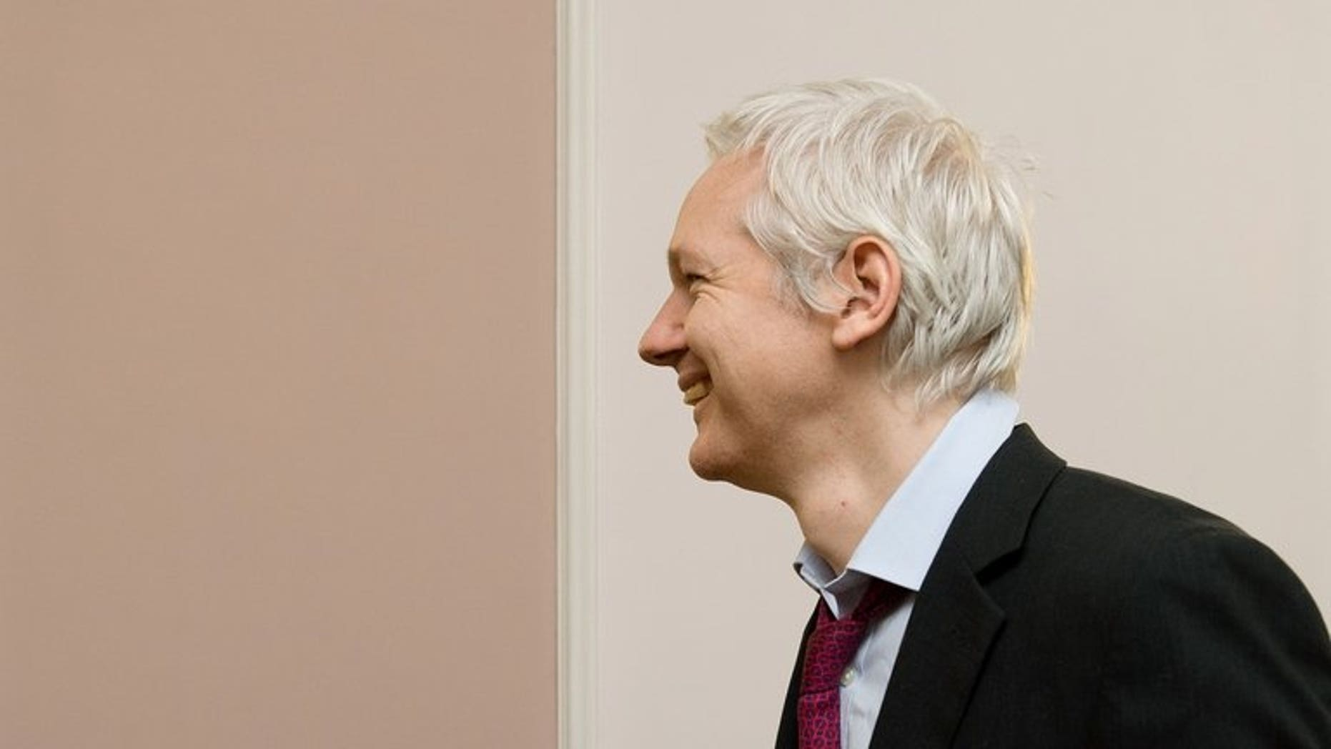 """Wikileaks founder Julian Assange arrives for a photocall with French politician Jean Luc Melenchon inside the Ecuadorian embassy in central London, on December 6, 2012. A year after seeking refuge at the Ecuadorian embassy in London, Assange remains fearful of US """"revenge"""" over the WikiLeaks disclosures and aware that the diplomatic deadlock over his case may continue for months, if not years."""