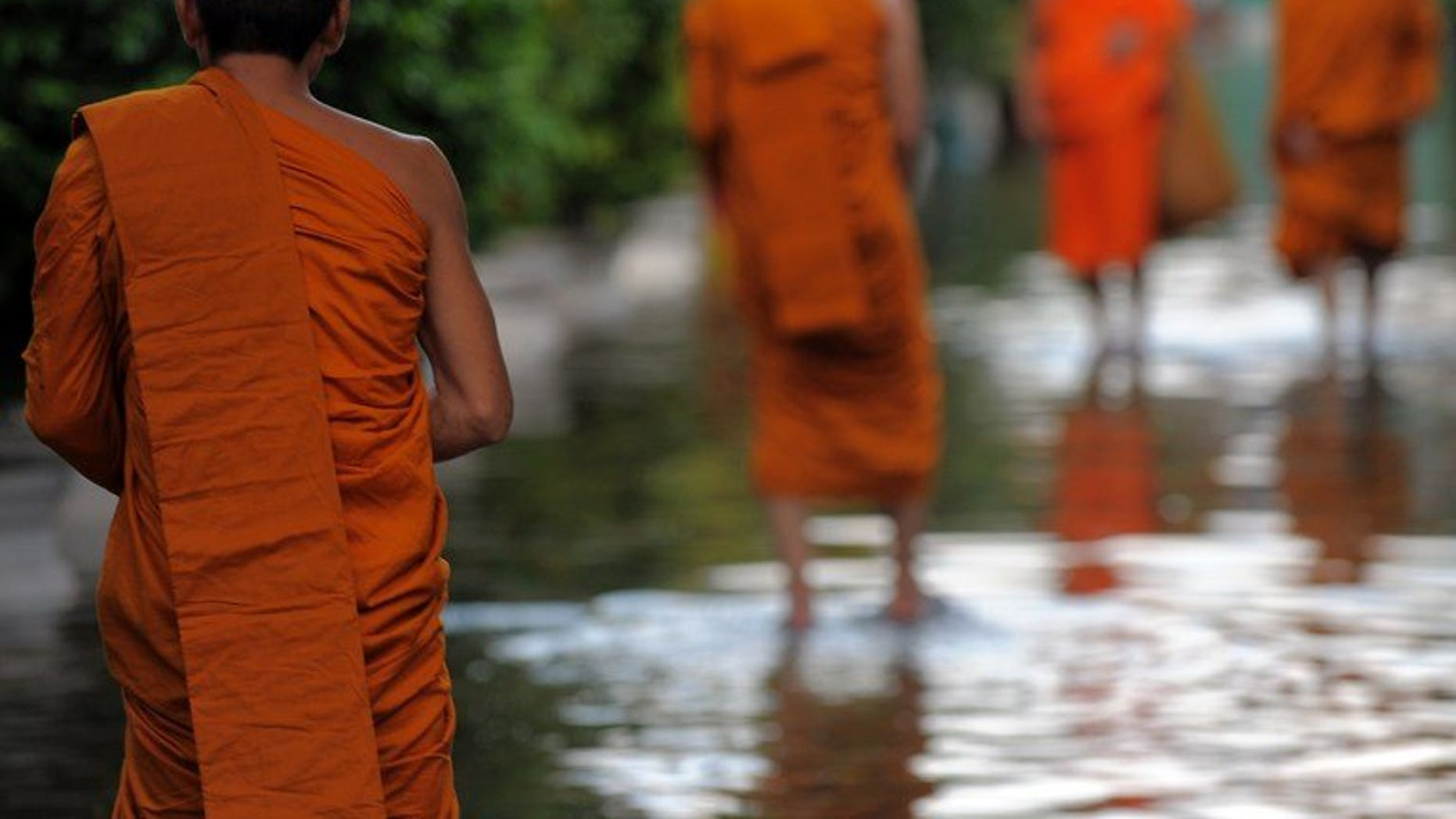 Thai Buddhist monks walk through floodwaters at a pagoda in Bangkok on October 27, 2011. Thai police said Wednesday they had arrested two monks for procuring a 14-year-old boy to perform sexual acts with an abbot, in the latest scandal to shake the kingdom's Buddhist clergy.
