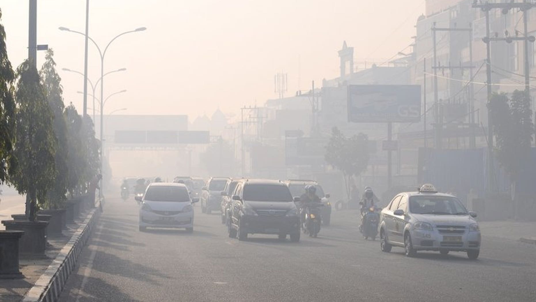Commuters travel on a road blanketed by haze due to nearby forest fires, in Pekanbaru city, capital of Riau province on Sumatra island on June 19, 2013. Indonesia plans to use weather changing technology to try to unleash torrents of rain and extinguish raging fires on Sumatra island that have cloaked neighbouring Singapore in thick haze, an official said Wednesday.