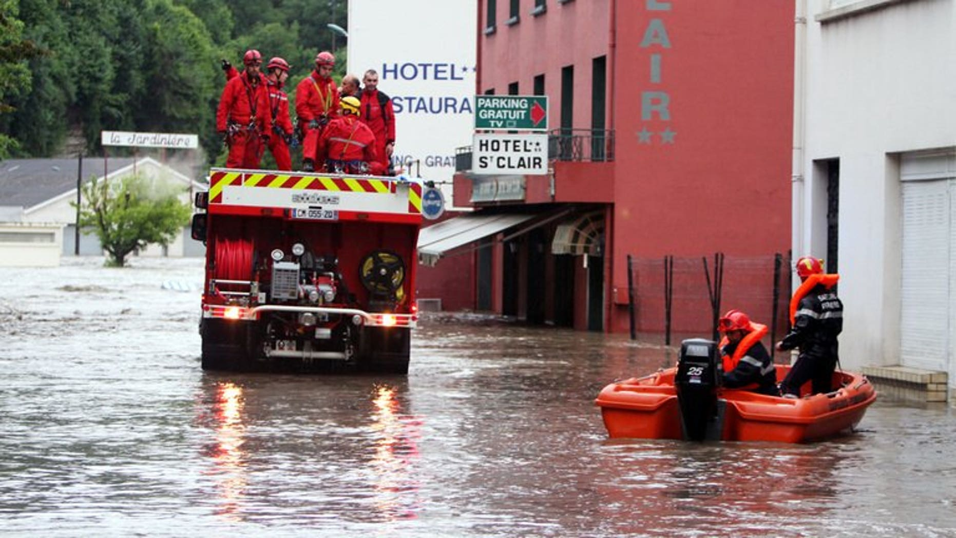 Firemen are at work in Lourdes where the Gave de Pau, the river passing through the town, flooded some pilgrimage areas on June 18, 2013. Flash floods in southwestern France killed an elderly woman as the inundated grotto at the Roman Catholic pilgrimage site of Lourdes remained closed for a second day