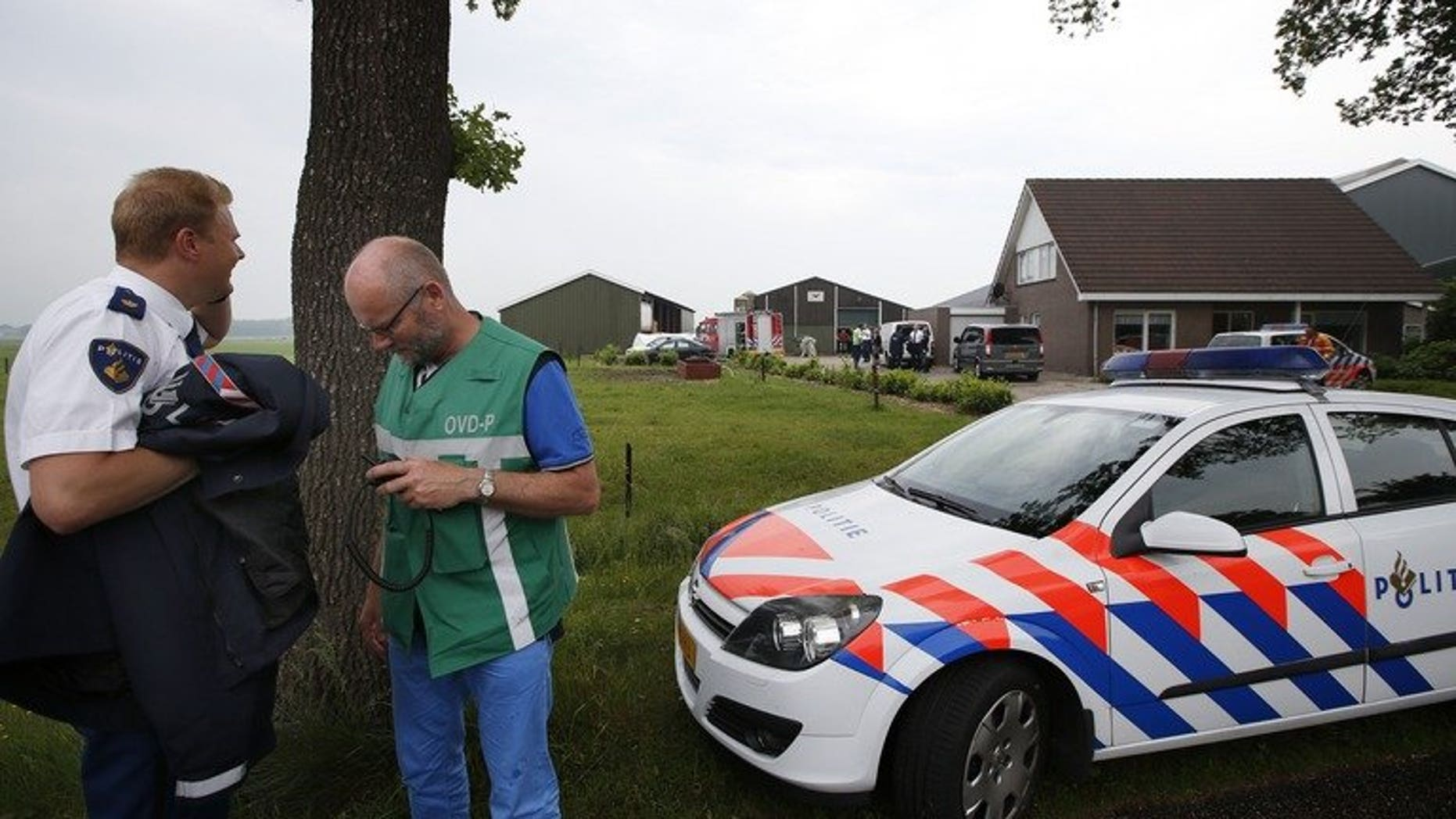 Policemen and rescue workers stand in front of a farm in Makkinga in northern Netherlands, where three men were killed and on man injured after an accident in a manure silo on June 19, 2013. Three farmworkers died after falling into a manure silo in the northern Netherlands, with a survivor flown to hospital in a critical condition
