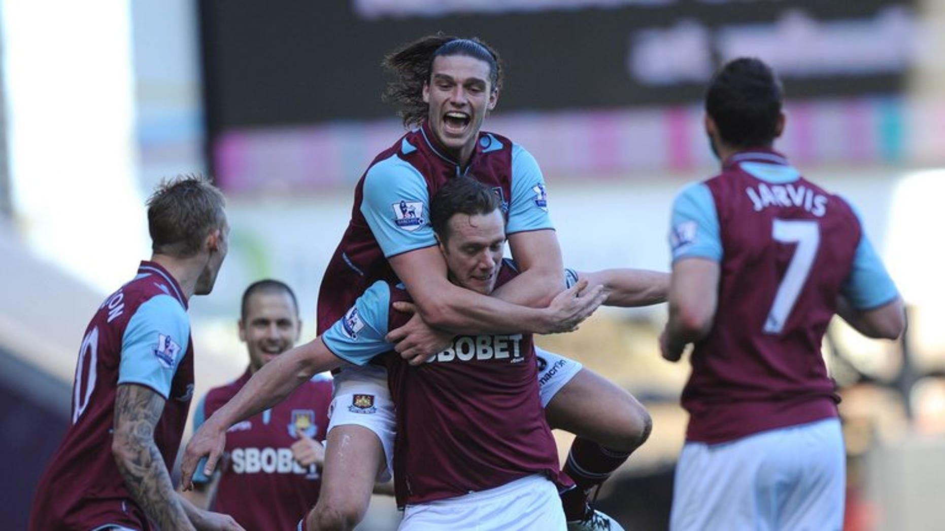 Andy Carroll (top) helps Kevin Nolan (below) celebrate a goal for West Ham against Wigan at Upton Park on April 20. England striker Carroll has completed his move from Liverpool to West Ham United, the east London club says.