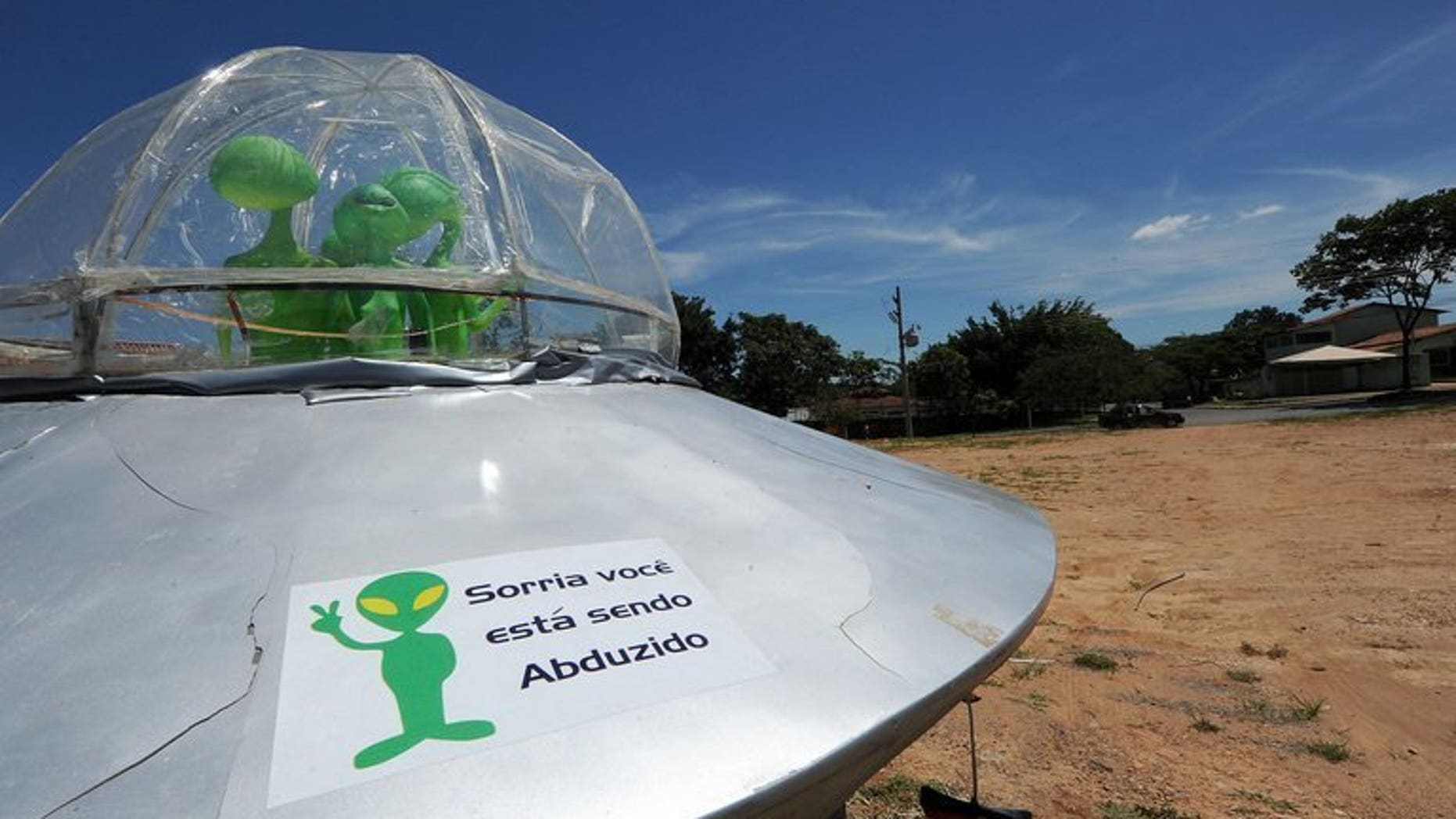 """File picture shows a mock UFO with a sign reading """"Smile, you are being abducted"""" north of Brasilia, December 2012. Britain's defence ministry shut down its UFO unit four years ago after concluding that extra-terrestrials likely did not exist, and in any case did not pose a threat, previously secret files released on Friday showed."""