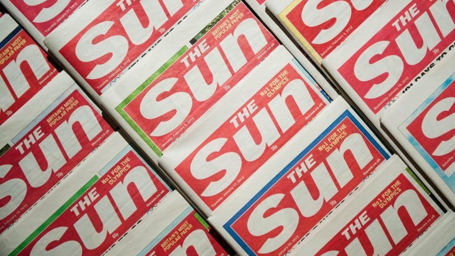Picture shows an arrangement of copies of The Sun tabloid on February 13, 2012. Two journalists from Rupert Murdoch's The Sun were charged in Britain on Friday, accused of paying officials for information about hospital patients, the royal family and ongoing police investigations.