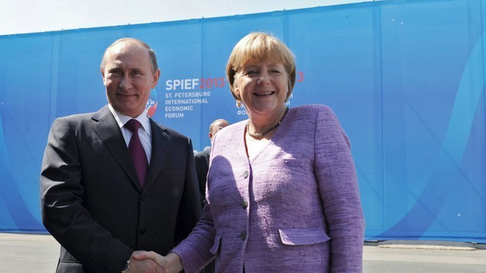 Russia's President Vladimir Putin (L) and Germany's Chancellor Angela Merkel meet during an International Economic Forum in St Petersburg, on June 21, 2013. Putin and Merkel on Friday announced that they would both attend the opening of a Saint Petersburg exhibition that includes treasures taken by the Red Army at the end of World War II.