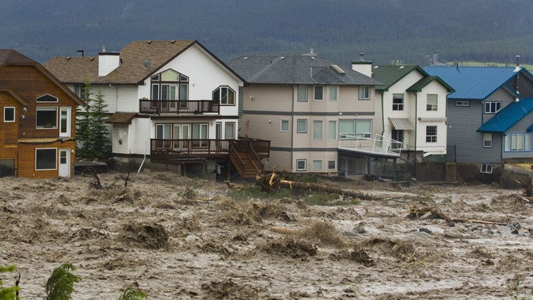 Damaged houses along the edge of floodwaters in Cougar Creek in Canmore, Alberta, western Canada pictured on June 20, 2013. Flooding forced the evacuation on Friday of some 100,000 people in Calgary and nearby towns in the heart of the Canadian oil patch in Alberta.