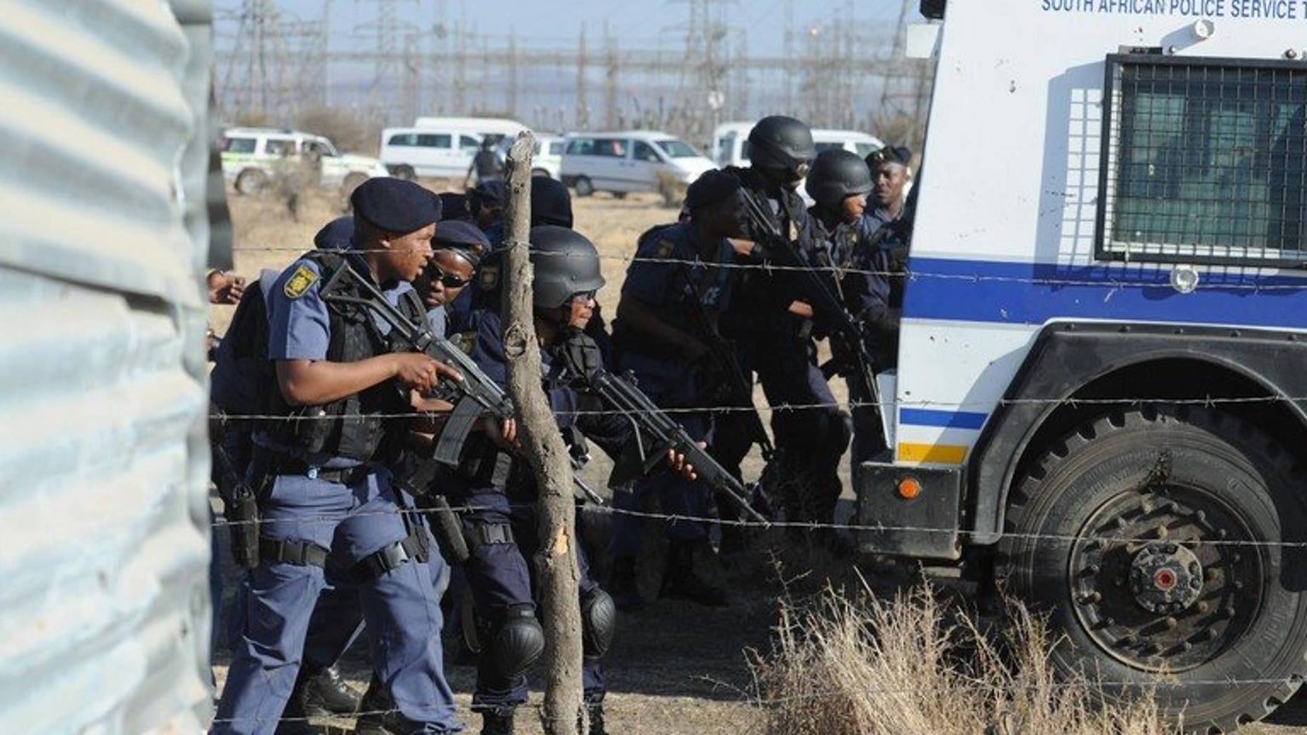 Police officers look at protesting miners near a platinum mine in Marikana on August 16, 2012. South Africa's Marikana commission adjourned Friday with major questions remaining about how police came to shoot dead 34 miners and amid growing concerns about the inquest itself.