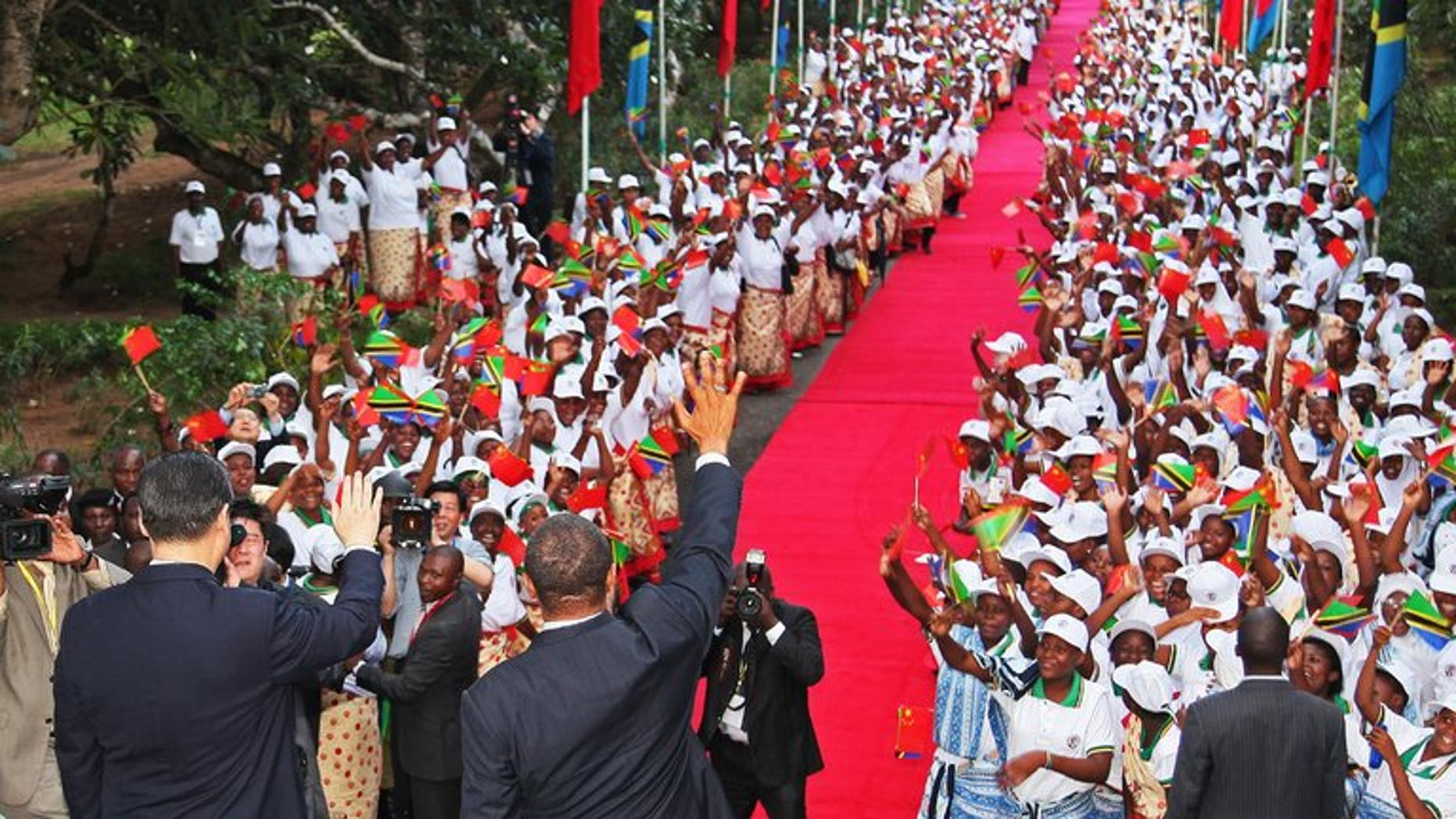 Chinese President Xi Jinping (L) and Tanzanian President Jakaya Kikwete (R) wave to crowds in Dar Es Salaam on March 24, 2013. World leaders visit Africa relatively little, but Tanzania is preparing to host US President Barack Obama just three months since a state visit the Chinese leader.
