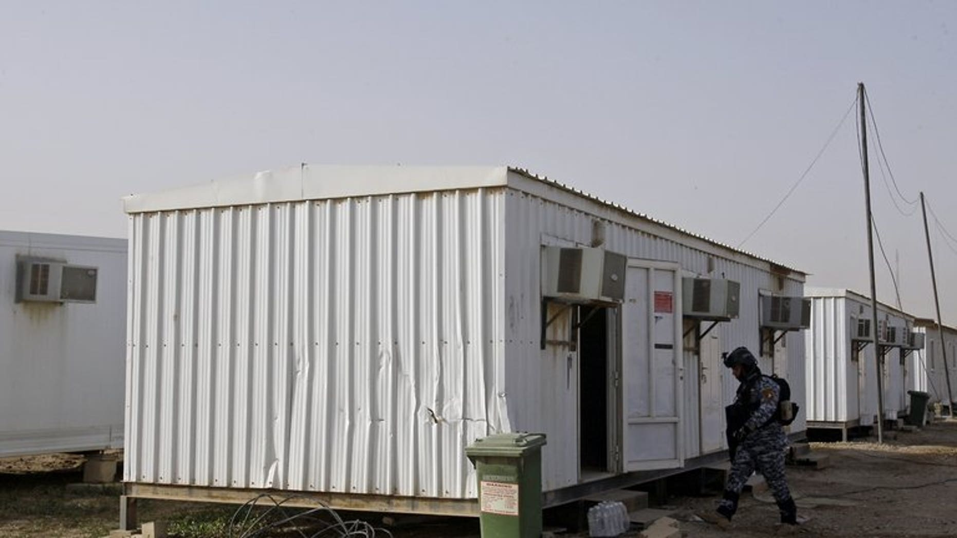 An Iraqi soldier inspects prefabricated houses at Camp Liberty, on February 17, 2012. Seventy-one members of an exiled Iranian opposition group based at Camp Liberty have been relocated to Albania, the UN said, a week after the camp suffered deadly mortar attacks.