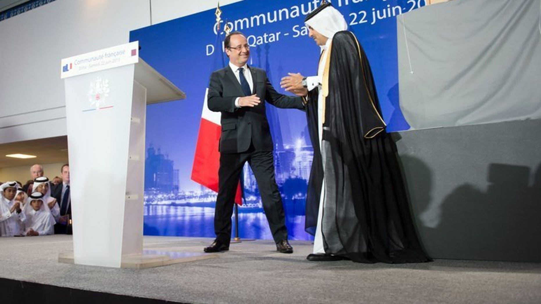 France's President Francois Hollande (L) is congratulated by Qatar's Attorney General Ali bin Mohsen bin Fetais al-Marri (R), in Doha, June 22, 2013. Hollande arrived in Qatar for talks on the deadly Syrian conflict and economic ties with the gas-rich Gulf state.