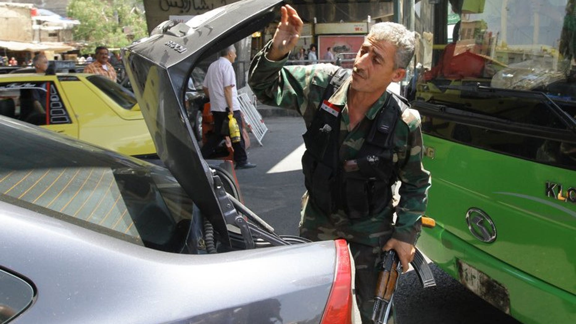 A Syrian soldier checks the trunk of a car at a checkpoint in Damascus on June 17, 2013. A suicide attack Sunday hit the northern Damascus district of Rukn al-Din, said Syrian state television, which also cited an unknown number of casualties