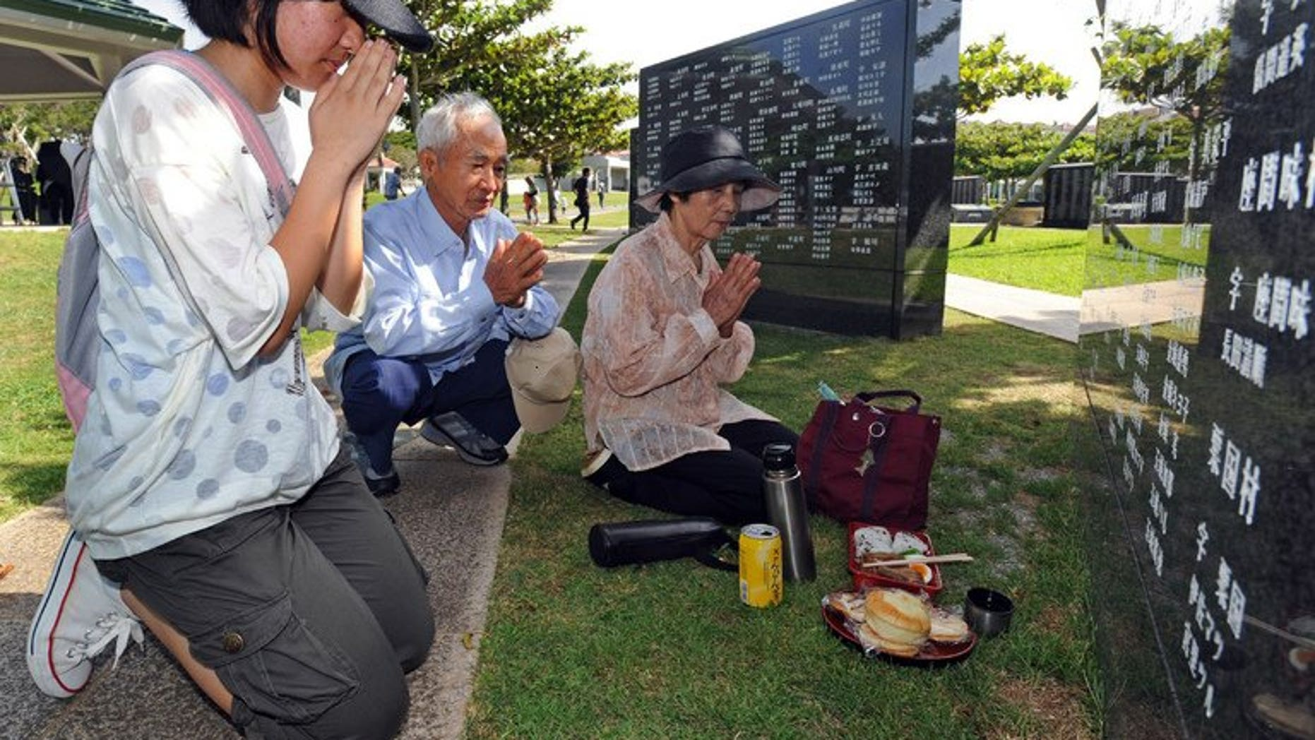 """Relatives of victims killed at the 'Battle of Okinawa' pray during a memorial service at the Peace Memorial Park in Itoman, on June 23, 2013. Okinawa has marked the 68th anniversary of a bloody World War II battle, with Japan's prime minister vowing to """"lighten the burden"""" of local residents opposed to a heavy US military presence on the southern Japanese island."""