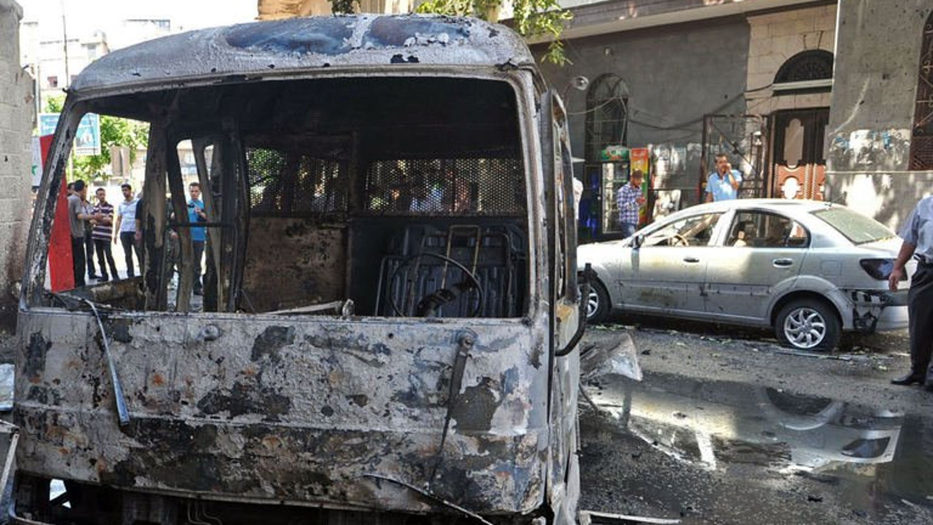 A handout picture released by the Syrian Arab News Agency (SANA) on June 23, 2013, shows civilians inspecting burnt out vehicles following an attack in the capital Damascus.