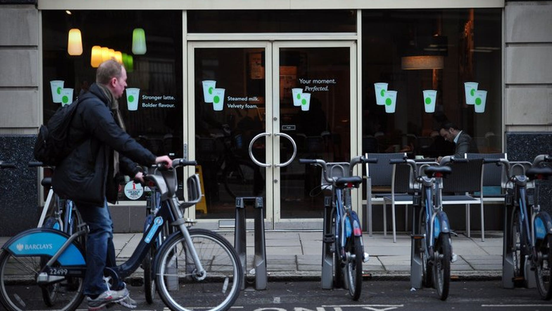 A man parks his hire bicycle outside a branch of Starbucks in central London on February 1, 2013. The US-based coffee giant has said it had paid ??5 million in British corporation tax and will pay another ??15 million by next year after facing a backlash from lawmakers and customers over non-payment.