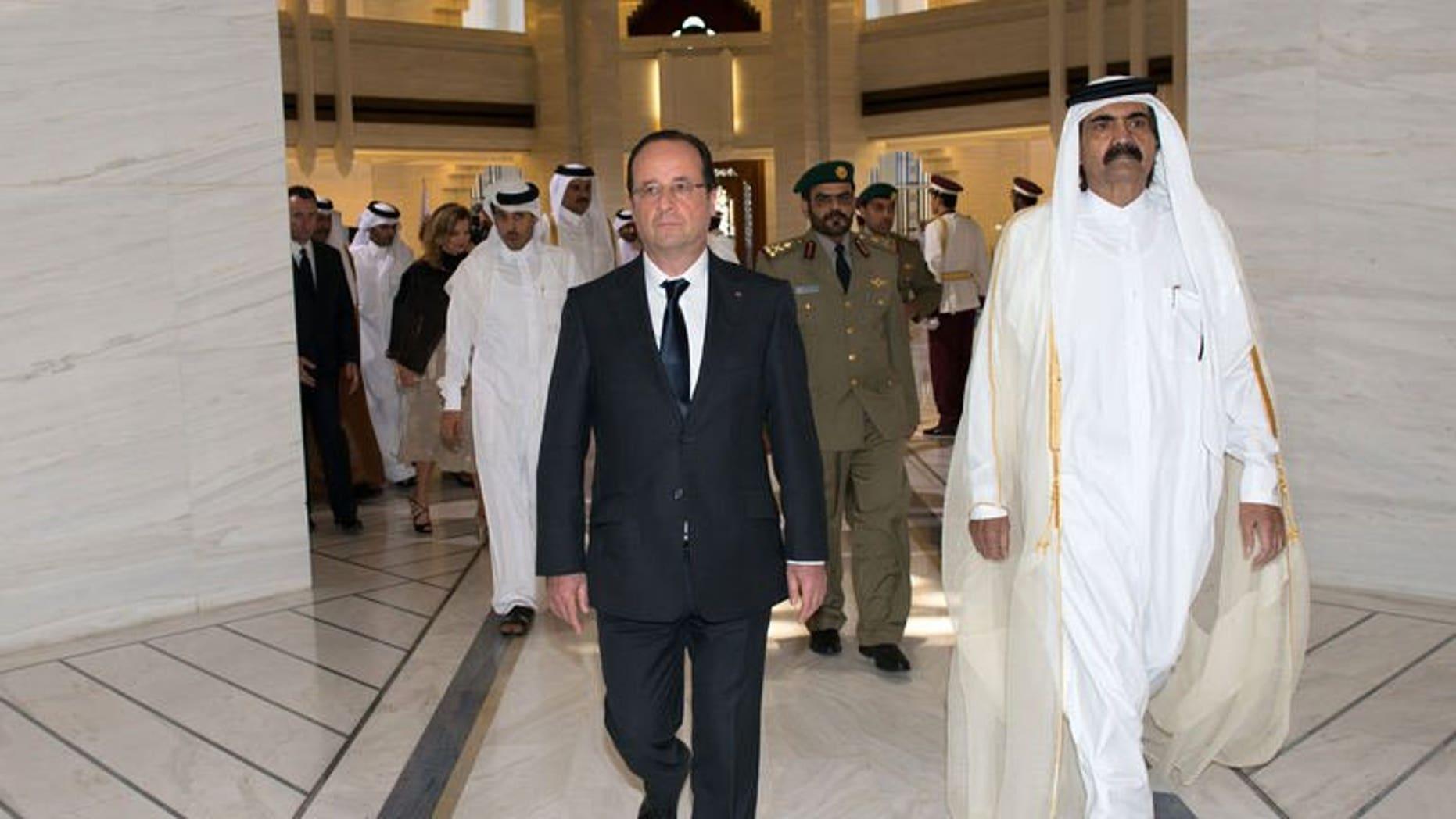 "French President Francois Hollande (left) is greeted by Qatari Emir Sheikh Hamad bin Khalifa al-Thani at the Emiri Diwan in Doha, on June 23, 2013. Hollande has urged rebels in Syria to ""retake"" zones that have fallen into the hands of extremist Islamist groups."