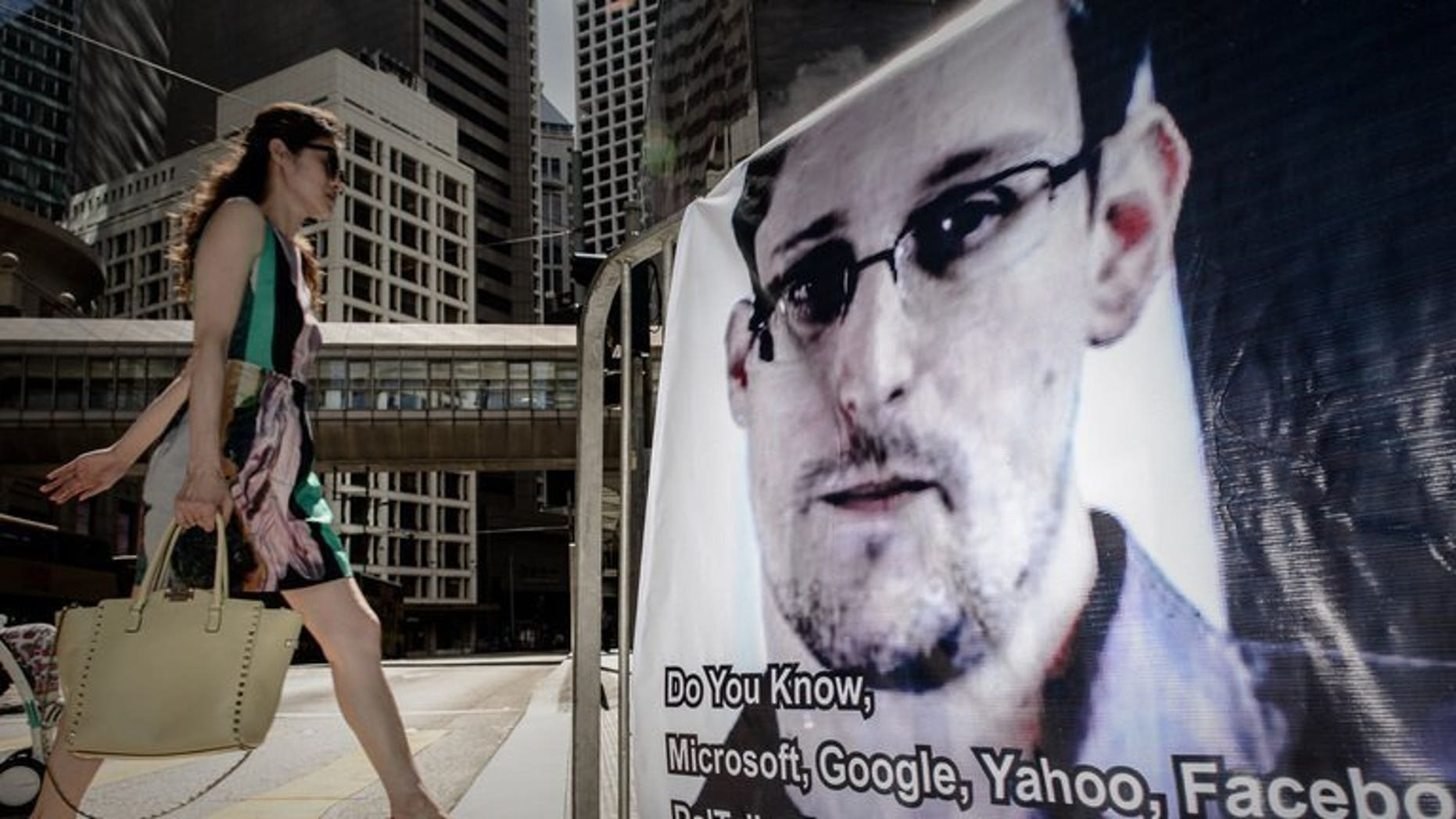 A woman walks past a banner displayed in support of former US spy Edward Snowden in Hong Kong on June 18, 2013. Snowden has requested asylum in Ecuador, the Ecuadoran foreign minister said Sunday, as he seeks to escape US justice for revealing secrets of a vast phone and Web surveillance drive.