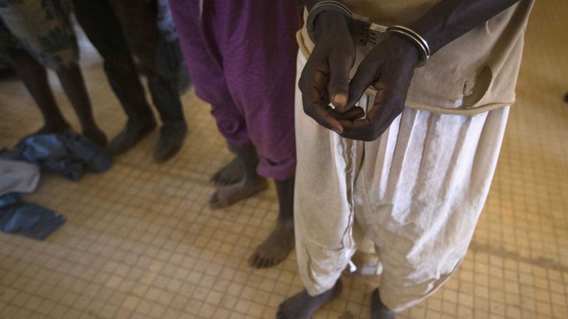 "Prisoners are taken out of a jail in the northern Malian city of Gao on February 26, 2013 to be transferred to Bamako, where they were to be judged on charges of belonging to MUJAO, an Al-Qaeda offshoot. MUJAO on Sunday offered to free one of a group of Algerian diplomats kidnapped last year in exchange for the release of three ""mujahedeen"" held in Algeria."