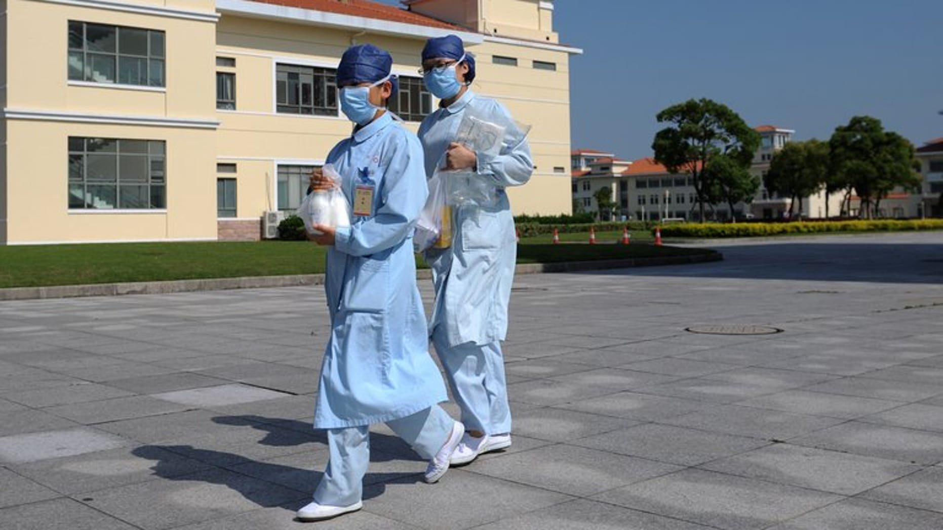 """In this photo taken on May 14, 2013 two nurses walk outside an isolation hospital in southwest Shanghai. The H7N9 bird flu that hit China this year killed over a third of hospitalised patients, said researchers Monday who labelled the virus """"less serious"""" but probably more widespread than previously thought."""