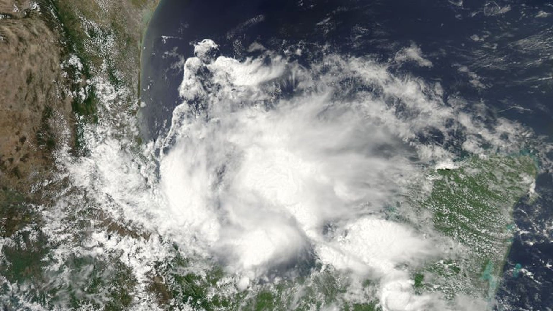 This June 19, 2013 NASA satellite image shows Tropical Storm Barry. An eight-year-old child and his mother were killed in southern Mexico after being swept away in a river during the storm, bringing the death toll to three.