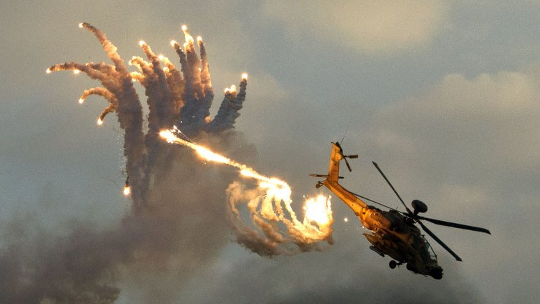 An Israeli Apache helicopter launches anti-missile flares during an air show on December 27, 2012. The Israeli air force attacked targets in the Gaza Strip overnight, following rocket fire from the Palestinian territory into southern Israel, sources from both sides of the conflict said.