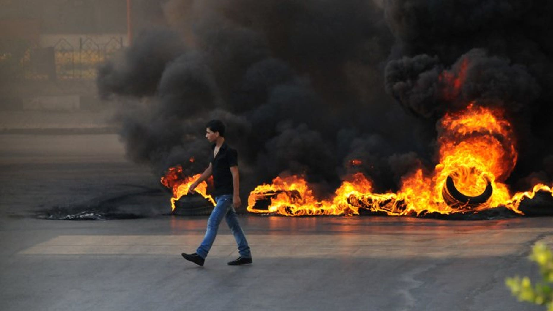 A youth walks past burning tyres in the northern Lebanese city of Tripoli on June 23, 2013 during protests in support of Sunni cleric Sheikh Ahmad al-Assir. At least 12 soldiers have been killed in less than 24 hours of clashes with Assir supporters in Sidon.
