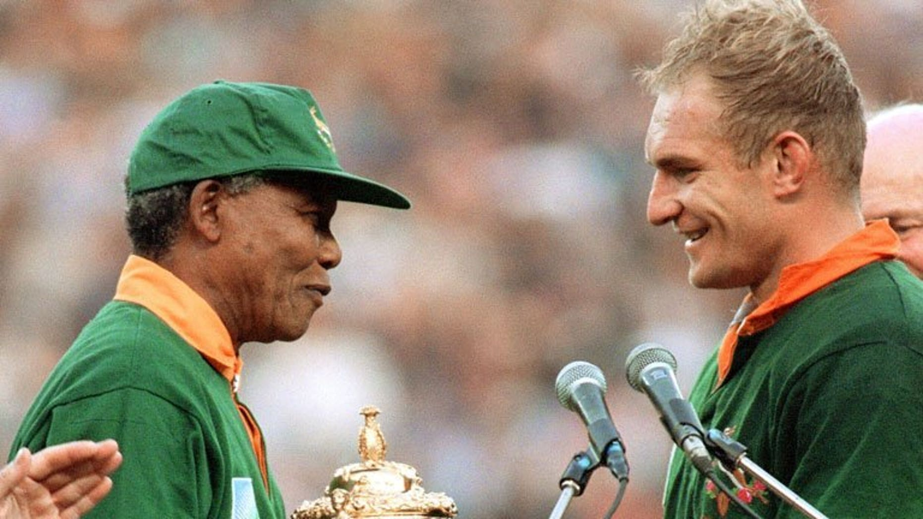 South Africa's then president Nelson Mandela (L) hands national rugby team captain Francois Pienaar the Webb Ellis Cup after South Africa won the 1995 Rugby World Cup final at Ellis Park Stadium, Johannesburg on June 24, 1995. With Mandela critically ill in hospital, South Africans on Monday recalled the day exactly 18 years ago when their team won the World Cup and Mandela won over the nation.