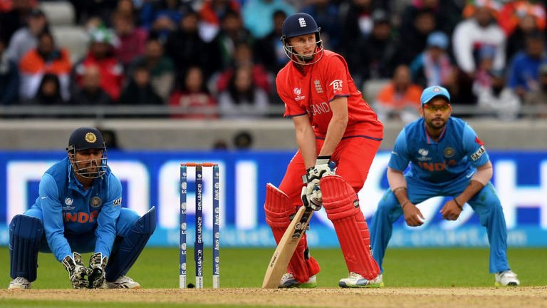 """England's Joe Root plays a shot as Indian Captain Mahendra Singh Dhoni (L) and India's Virat Kohli looks on during the 2013 ICC Champions Trophy Final cricket match between England and India at Edgbaston in Birmingham, central England on June 23, 2013. England said Monday rising star Root was """"currently the best opening partner for Alastair Cook"""" as they left Nick Compton out of their squad."""