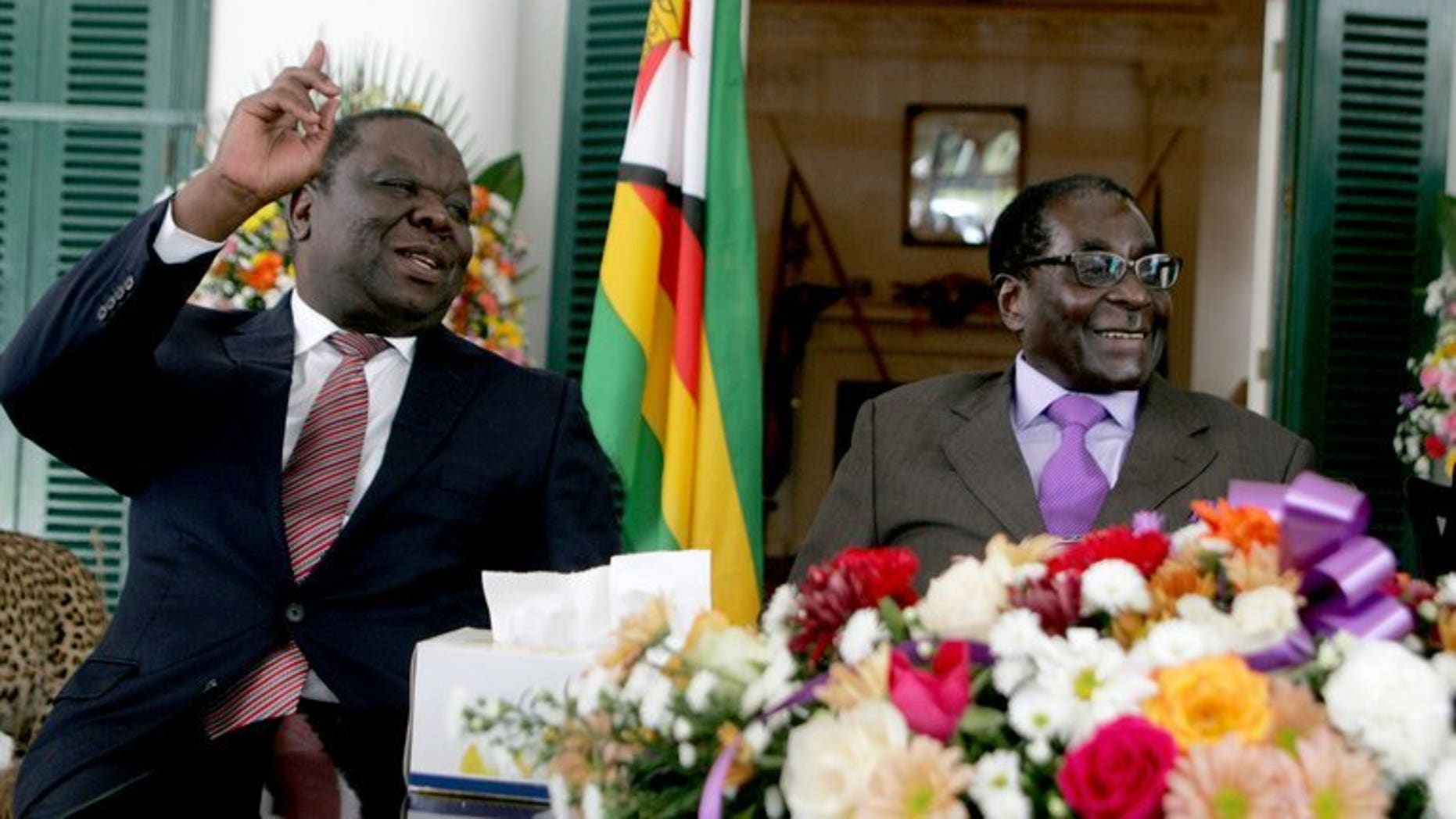 Zimbabwe's Prime Minister Morgan Tsvangirai (L) and President Robert Mugabe at the conclusion of the constitution-making process at State House on January 17, 2013 in Harare. Tsvangirai has filed an application with the country's top court for a delay of elections to allow key reforms to take effect, court papers showed.