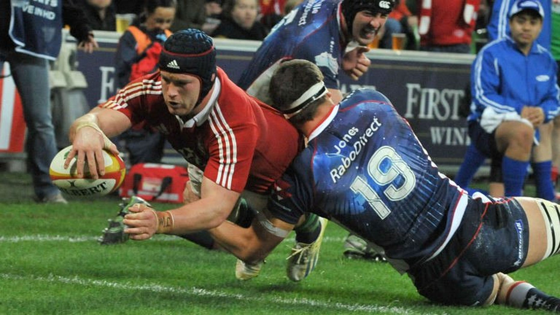 British and Irish Lions' flanker Sean O'Brien (left) dives over the try line to score a try against the Melbourne Rebels on June 25, 2013. The Lions scored five tries to beat the Melbourne Rebels 35-0 in their tour game in Melbourne.