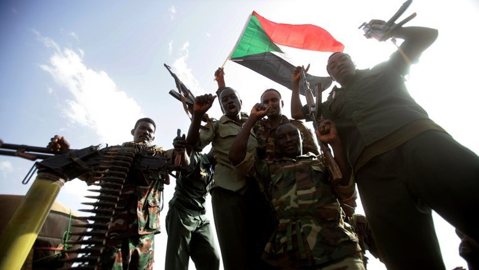 Sudanese soldiers cheer as they hold up their guns and a national flag during President Omar al-Bashir's visit to Sudan's main petroleum centre of Heglig on April 23, 2012. A new general took command of the Sudan Armed Forces (SAF) on Tuesday after what analysts called humiliating attacks by anti-government rebels.