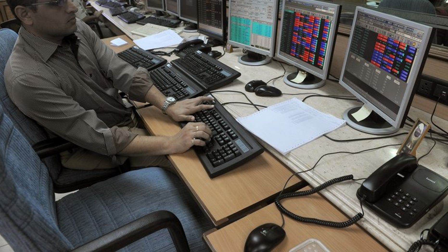 An Indian stockbroker watches share prices on trading terminals at a brokerage house in Mumbai on October 4, 2012. India's market regulator on Tuesday announced an overhaul of existing regulations for foreign investors, in a bid to attract crucial inflows to the country's capital markets.