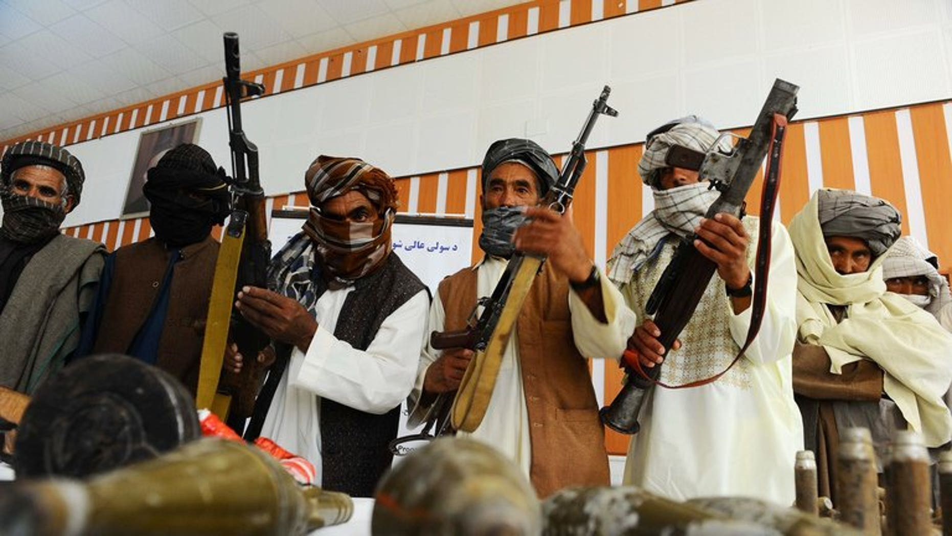 Former Taliban fighters show their weapons to the media, after joining Afghan government forces, in Herat, on June 26, 2013. The US said on Thursday that it expected the Taliban to continue to mount attacks in Afghanistan even as the rebels hold peace talks from their new office in Qatar.