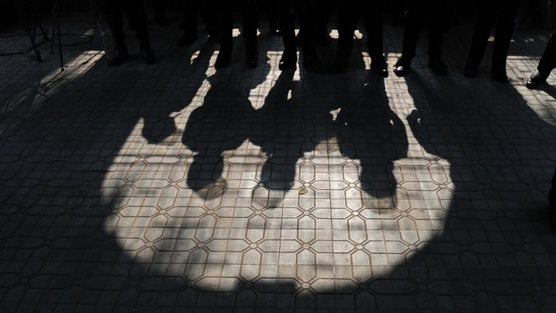 The shadows of Bangladeshi police as they stand guard in Dhaka, on January 21, 2013. A Bangladeshi court has sentenced nine junior opposition politicians to life in prison for murdering a newspaper journalist who had published a series of reports on corruption, a prosecutor said Friday.