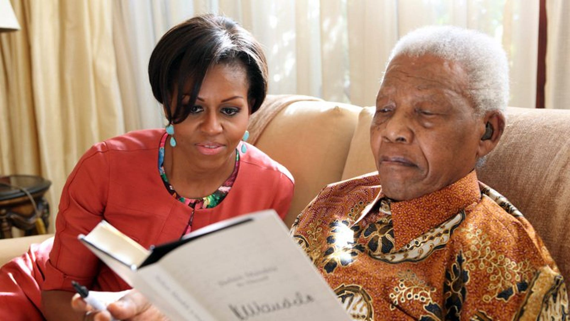 """Nelson Mandela with Michelle Obama at Mandela's home in Johannesburg in 2011. US President Barack Obama on Saturday hailed the """"moral courage"""" of Nelson Mandela, which he said was an inspiration to the world."""