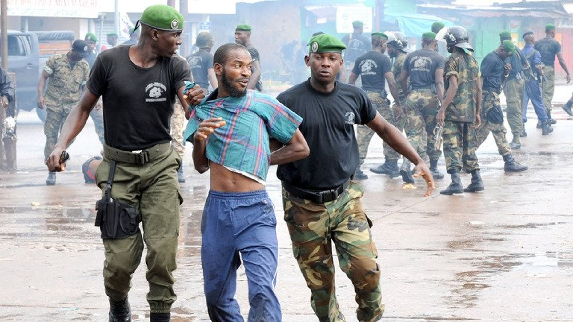 Guinean police arrest a protester on September 28, 2009 in front of the biggest stadium in the capital Conakry during a protest banned by Guinea's ruling junta. Guinean judges have charged a minister in connection with the Conakry Stadium massacre in which at least 157 protesters were killed.