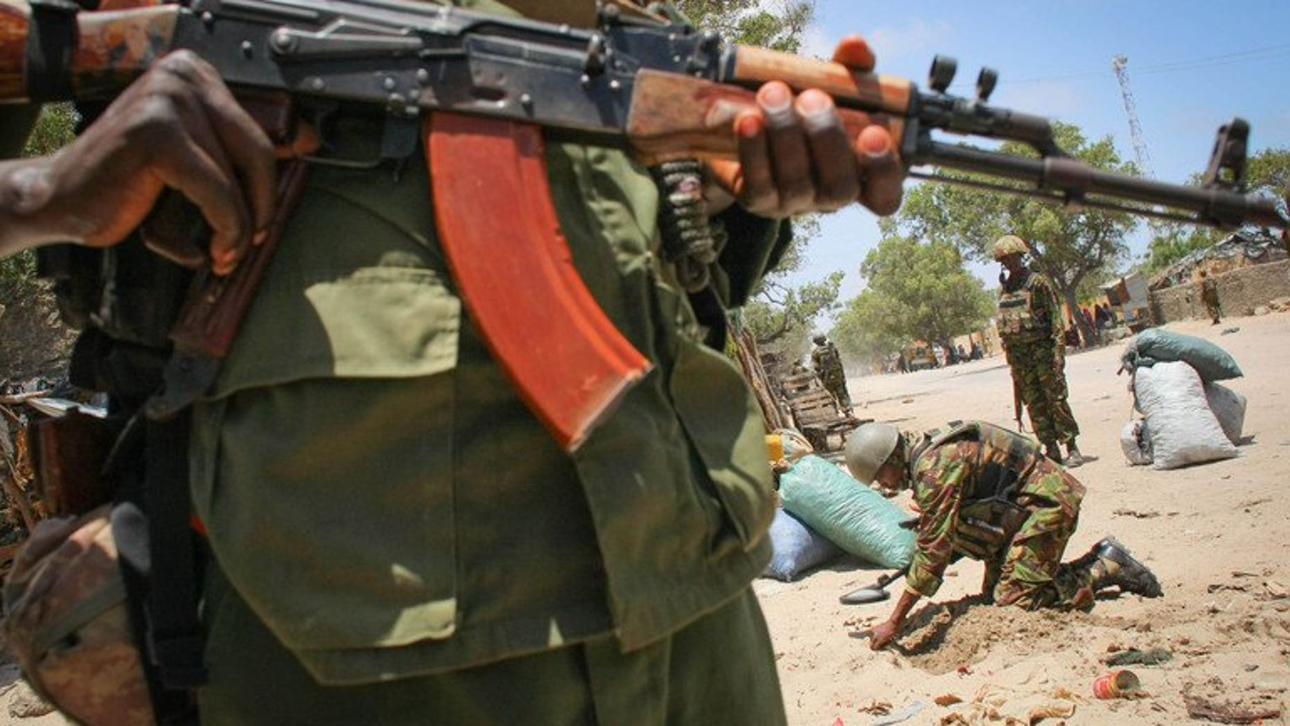 A fighter of the Ras Kimboni Brigade militia stands guard as a team searches for explosives in the Somali port city of Kismayo, on October 7, 2013. At least five people have been killed in clashes between rival Somali warlords fighting for control of the city, residents said.