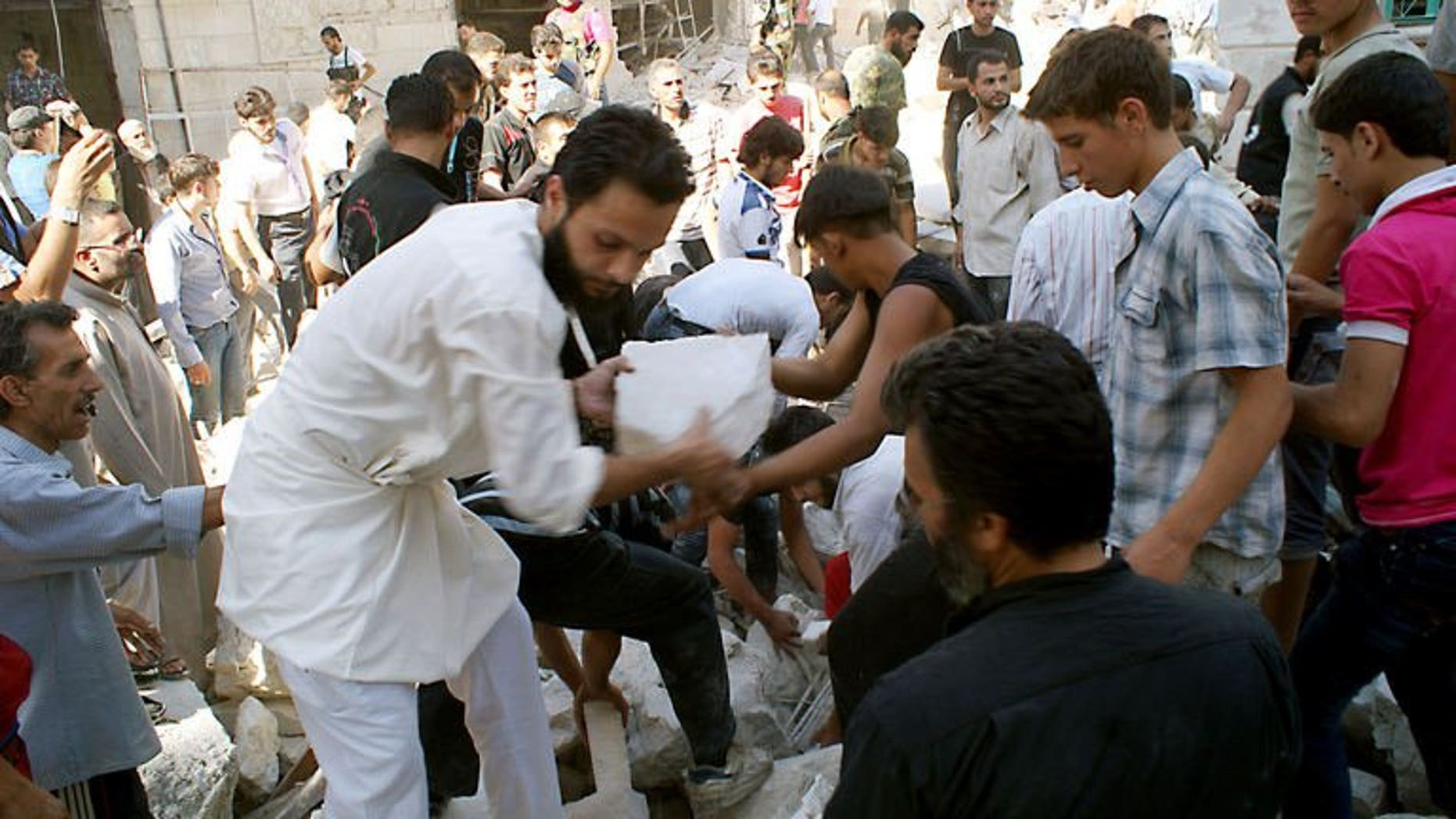 Rescuers and neighboors removes chunks of rubble from a partially collapsed building after a rocketed slammed into the side of a residential block located next to a mosque in Aleppo, Syria on June 29, 2013. The Gulf Arab nations and the European Union pledged Sunday to pool their efforts to help convene a peace conference on Syria, as they wrapped up a one-day ministerial meeting in Bahrain.