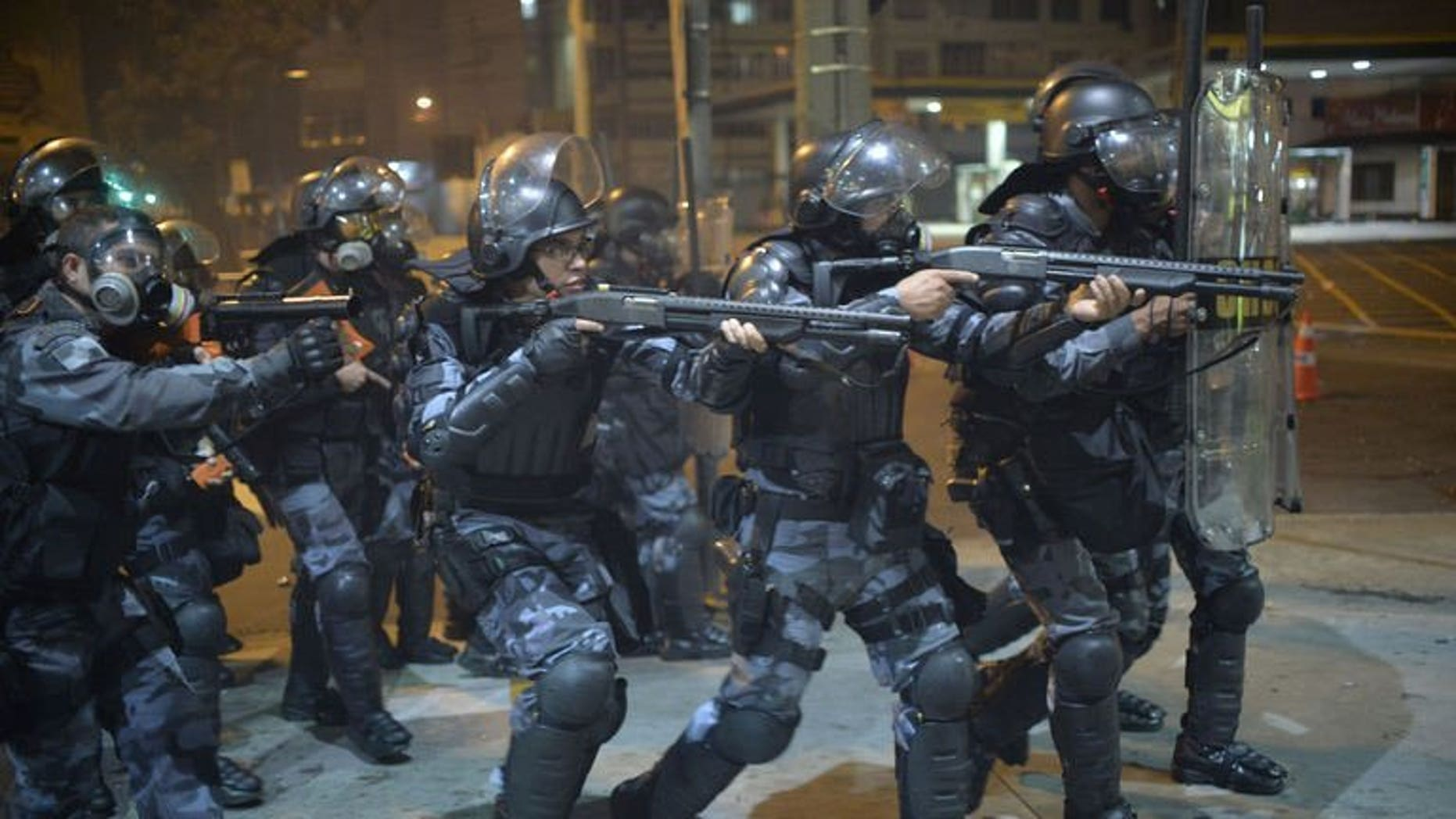 Anti riot police charge during a protest in a street near the Maracana stadium of Rio de Janeiro on June 30, 2013. Protesters clashed with police near Rio's iconic Maracana stadium Sunday, only minutes before the start of the Brazil-Spain final of the Confederations Cup, AFP correspondents reported.
