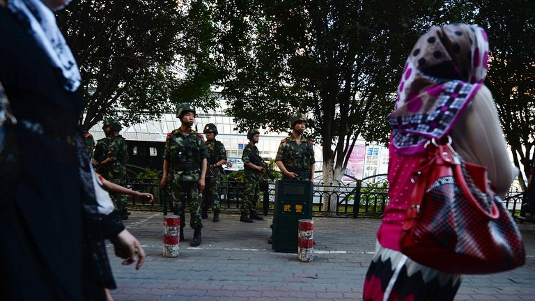 """A woman walks by Chinese paramilitary police in Urumqi, Xinjiang, on June 30, 2013. Western media are encouraging """"terrorism"""" in Xinjiang by misrepresenting violence in the region as ethnic conflict between minority Uighurs and Han Chinese, state-run media said."""