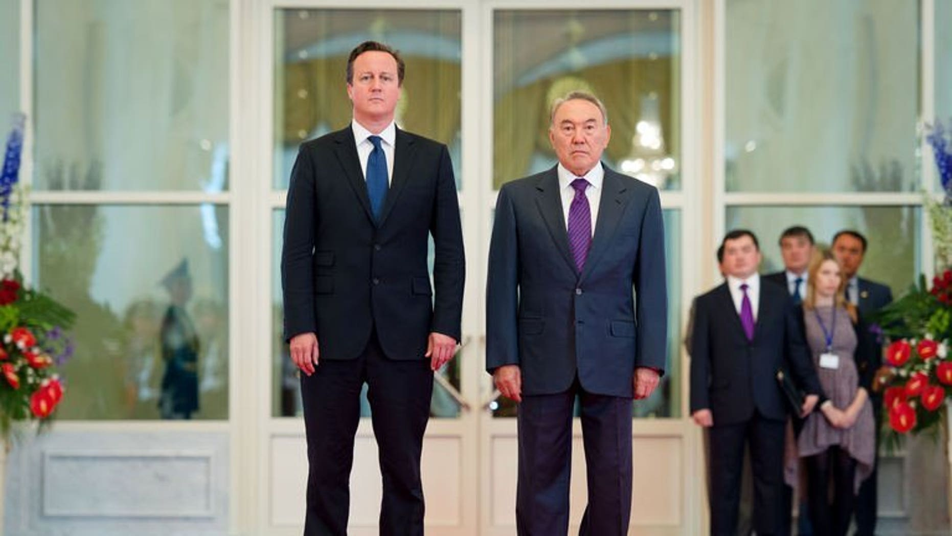 British Prime Minister David Cameron (L) and Kazakhstan President Nursultan Nazarbayev stand together as they listen to the national anthem in the Presidential Palace in Astana, Kazakhstan on July 1, 2013. Cameron unveiled a massive oil and gas processing plant on the shores of the Caspian Sea on Monday during his first visit to ex-Soviet Kazakhstan.