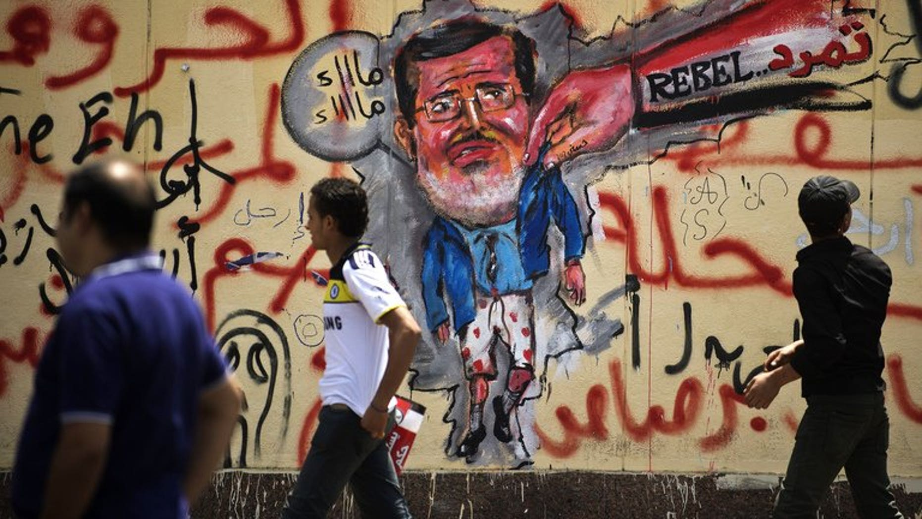 Egyptian protesters walk past graffiti against Mohamed Morsi on the wall of the presidential palace in Cairo, on July 1, 2013. Egypt's ministers of tourism, environment, communication and legal affairs have tendered their resignations a day after massive protests against Morsi swept the country, a senior government official told AFP.