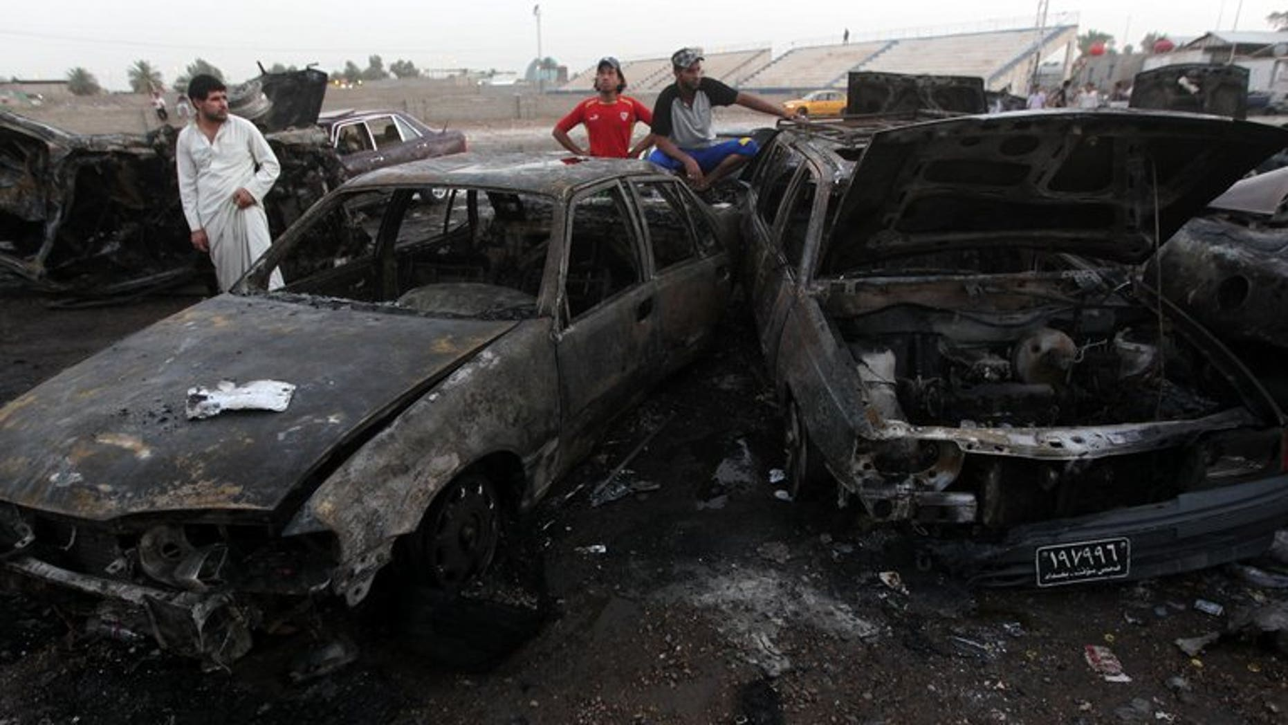 Iraqi men gather at the scene of one of a car bomb that exploded in Baghdad's Habibiyah area on May 27, 2013. More than 1,500 people were killed in Iraq in the past three months, twice the previous quarter's figure, fanning fears the politically-deadlocked country is slipping back into all-out bloodshed.