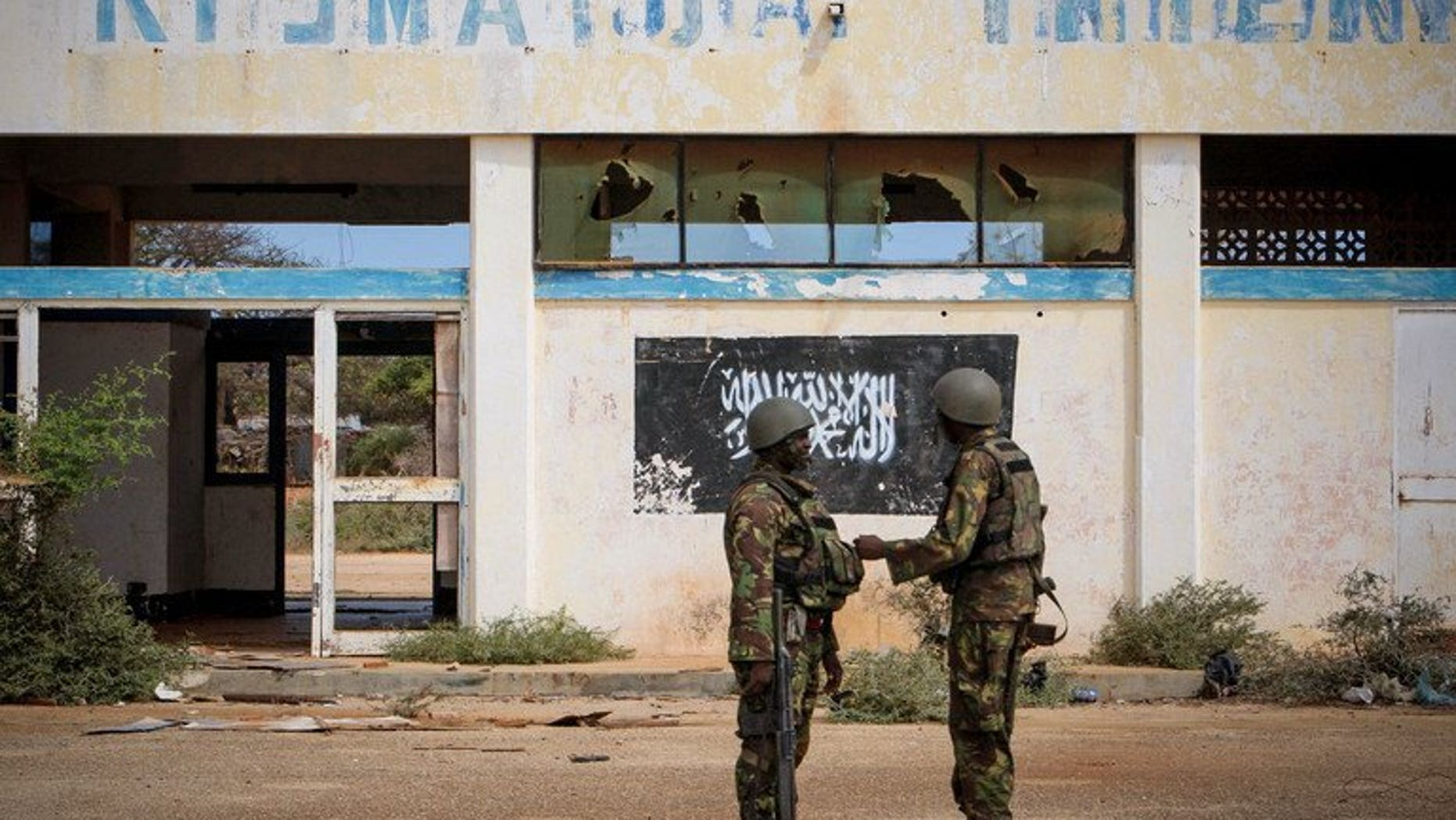 Photo released by the AU-UN Information Support Team on October 2, 2012 shows soldiers of the Kenyan contingent serving with the African Union Mission in Somalia near the black flag of the Al Qaeda-linked group Shebaab on the wall of Kismayo Airport. Somalia's government has demanded that Kenyan troops stationed in the volatile port city of Kismayo be replaced, accusing them of backing Shebab.