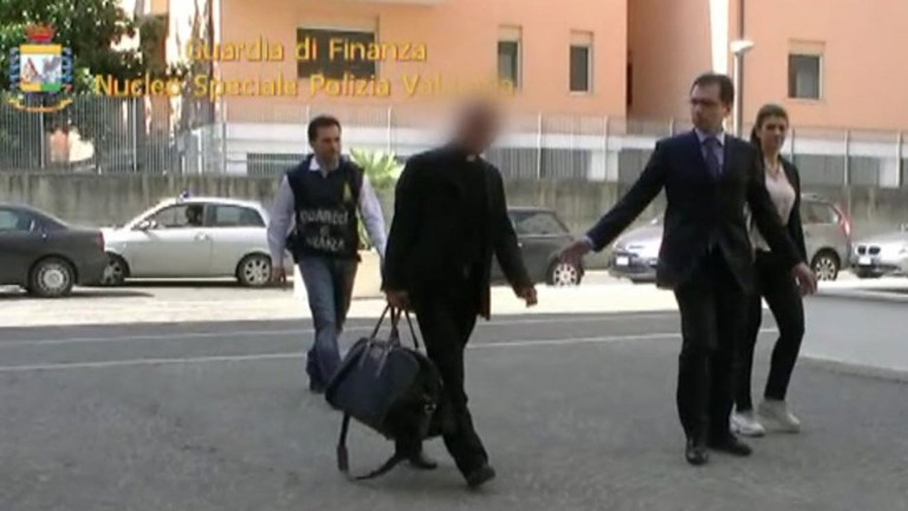 This handout picture taken from a video released by the Guardia di Finanzia Italian police on June 28, 2013 shows Nunzio Scarano (front left) being escorted by policemen after his arrest in Rome.